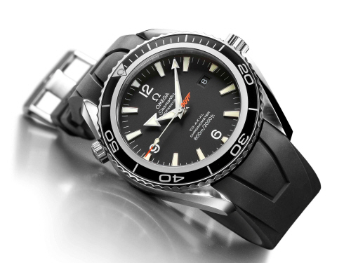 "The features indicating that this is a professional divers' watch are the watertight screw-in crown, a screw-in case back and the helium escape valve. Moreover it is water resistant to 600 meters (2000 feet). The matt black dial offers excellent clarity and the facetted arrowhead hour and minute hands also have luminous SuperLuminova inserts as well as a luminous arrowhead seconds hand with orange tip offers ultimate visibility down to the last second. Beneath the surface is Omega's calibre 2500 Co-Axial Escapement movement and has a power reserve of 48 hours. The bond watch is available with a 45.5 mm diameter case and a black rubber strap. This Limited Edition has exclusive features: the central second hand bears the ""007"" gun logo in orange, that recalls the code name of the famous MI6 secret agent. The stainless-steel case back is embossed with the ""Casino Royale"" logo as well as the series number of each Limited Edition watch. Restricted to 5,007 pieces, the Seamaster Planet Ocean ""Casino Royale"" is a must have for all the guys who idolize 007!"